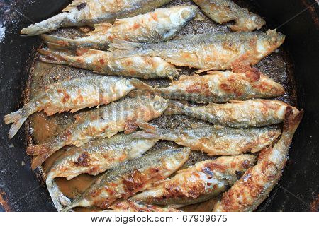 Fried fish in a frying pan closeup, culinary background