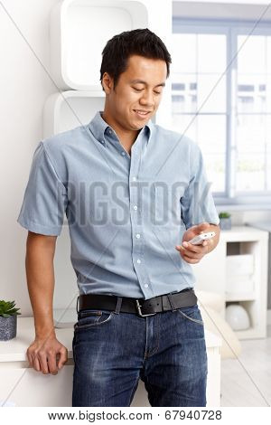 Young man using mobilephone, dialing or texting.