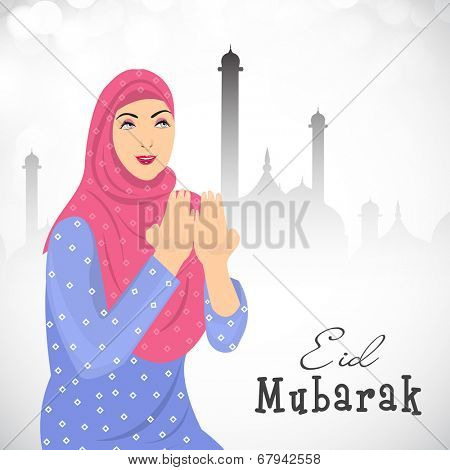 Religious Muslim girl praying in the front of mosque on grey background for the occasion of Muslim community festival Eid Mubarak celebrations.