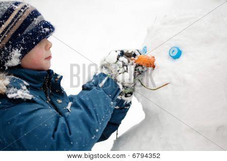 The boy makes a snowman.