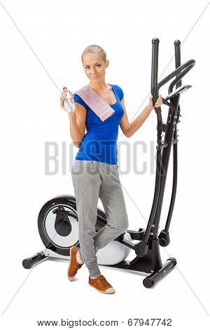 Young Woman Uses Elliptical Cross Trainer.