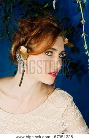 Romantic portrait of a beautiful woman with red hair and flowers in her hairstyle, wearing diamond ear cuff against blue grunge background