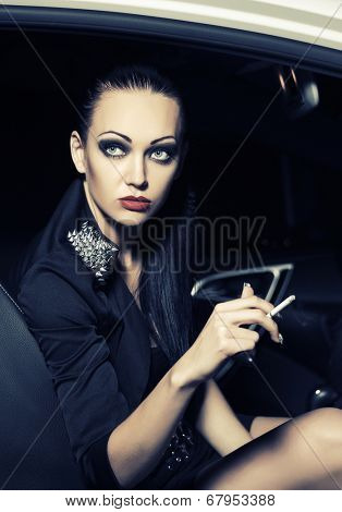Fashion woman smoking cigarette in a car