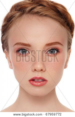Close-up portrait of young beautiful red-haired girl with freckles over white background