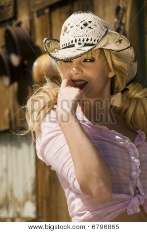 Blonde model in a pink blouse with a cowboy hat on
