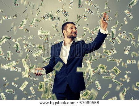 successful and smiley businessman catching money under dollar's rain