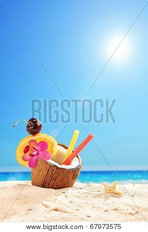 Vertical shot of an exotic cocktail in a coconut on a tropical beach on a sunny summer day