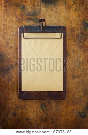 Old clipboard on old grungy wooden surface.