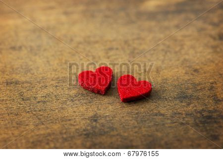 Two hearts on a old rustic wooden surface. Two red hearts for valentines day.