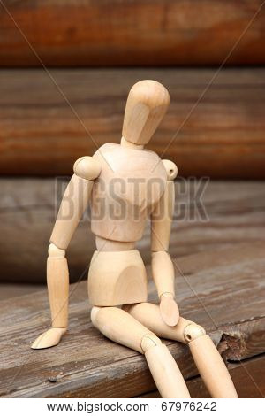 Wooden pose puppet sitting on wooden bench, outdoors
