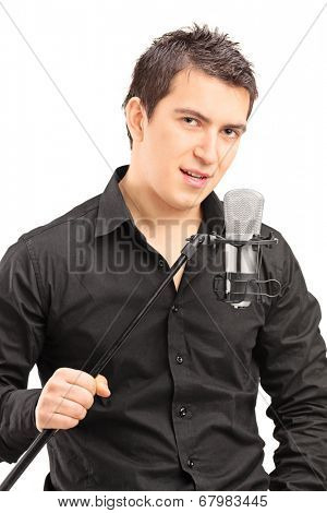 Elegant male singer holding a microphone isolated on white background