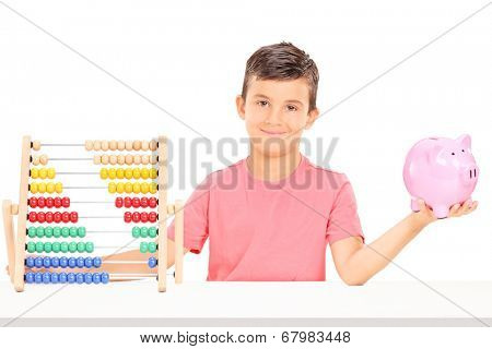Boy holding a piggybank seated at a table with an abacus isolated on white background