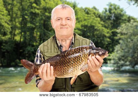 Mature fisherman showing his catch standing by a river outdoors