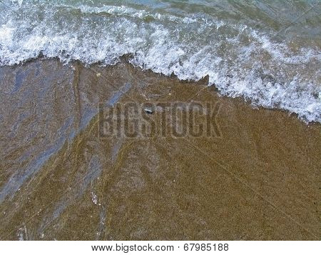 Yellow sand and whitecaps of the sea waves
