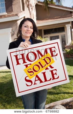 Woman Holding Sold Real Estate Sign In Front Of House