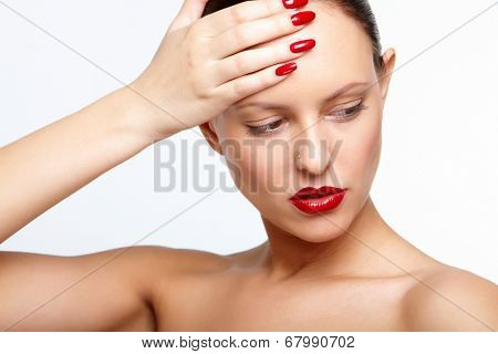 Posh woman with red lips and fingernails touching her forehead