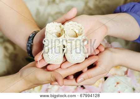 Hands Of Pregnant Woman And Husband With Bootees