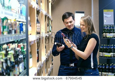 Couple choosing wine in a bottle store