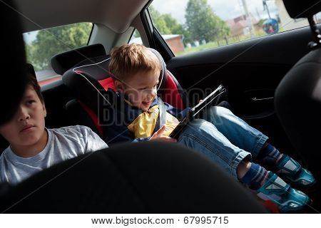 Two boys on the back seat of a car