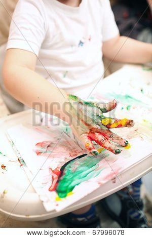 Boy painting with finger-paints