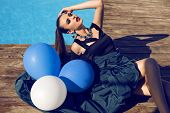 stock photo of beside  - fashion portrait of beautiful glamour young woman in elegant dress and bijou holding white and blue balloonslying beside a swimming pool - JPG
