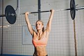 stock photo of lifting weight  - Beautiful strong young woman with barbell and weight plates overhead - JPG