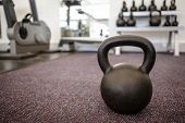picture of kettlebell  - Black kettlebell on the weights room floor at the gym - JPG