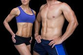 foto of physique  - Crossfit couple posing with hands on hips on black background - JPG