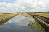 image of marshlands  - A constructed tidal river with high grass banks leads through marshland to the horizon with a cloudy sky - JPG