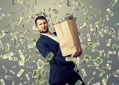stock photo of heavy bag  - handsome successful businessman holding heavy paper bag with money under dollar - JPG