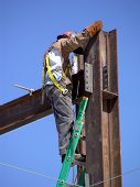 stock photo of high-rise  - Construction worker climbing to the top of a steel beam high rise building project - JPG
