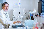 stock photo of scientific research  - Senior male researcher carrying out scientific research in a lab  - JPG