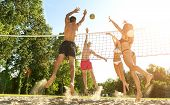stock photo of volleyball  - Group young Friends Playing Volleyball On Beach - JPG
