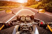 stock photo of driving  - Biker driving a motorcycle rides along the asphalt road - JPG