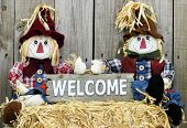 picture of rag-doll  - Boy and girl scarecrows sitting on straw bale holding rustic wood welcome sign - JPG