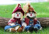 pic of scarecrow  - Boy and girl scarecrows sitting on grass by log next to lake - JPG