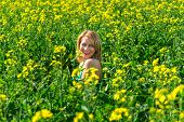 image of rape-field  - blond woman in a rape field - JPG