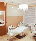 pic of beauty salon interior  - Interior of a beauty salon with a couch and equipment in a neutral decor of fresh white and shades of brown for skincare and consultations with a beautician and cosmetician - JPG