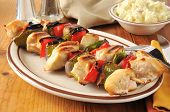 stock photo of kebab  - Chicken kebabs with potato salad on a rustic wooden table