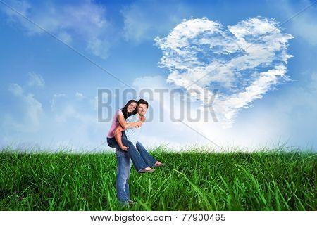 Young man giving girlfriend a piggyback ride against cloud heart