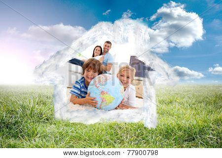Children playing with a terrestrial globe at home against sunny landscape