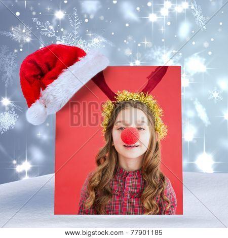 Festive little girl wearing red nose against snowflake design shimmering on blue
