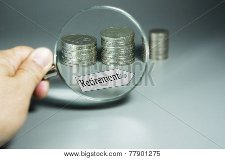 Magnifier, Retirement Tag, And Stack Of Coins In The Backdround