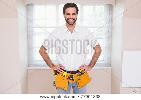 Handyman smiling at camera in tool belt in a new house