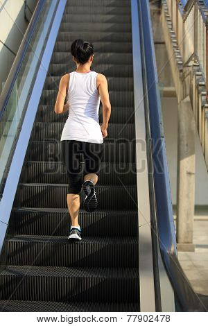 Runner athlete running on escalator stairs . woman fitness jogging workout wellness concept.