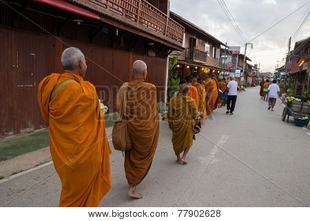 Buddhist Monk Walking To Let People Put Food Offerings In An Alms Bowl For Good Merit