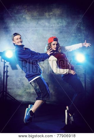 Two modern dancers over grunge background. Hip-hop. Urban, disco style.
