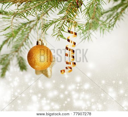Golden Christmas balls hanging on pine branch over sparkling holiday background