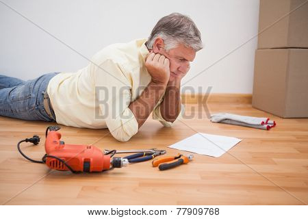 Man lying on floor reading tool instructions at home in the living room