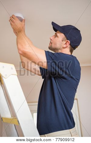 Focused handyman installing smoke detector with screwdriver on the ceiling